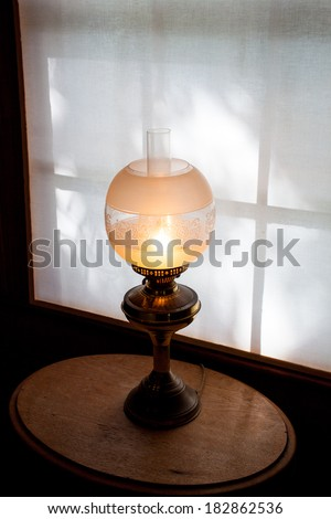 Vintage table lamp on a wooden table by the window in the house