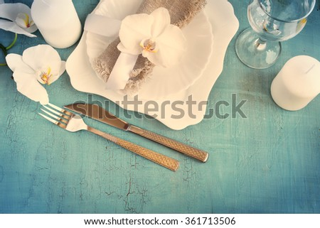 Vintage table setting with orchid decorations, candles, wineglass on a blue background. Top view. Tinted. Space for text - stock photo
