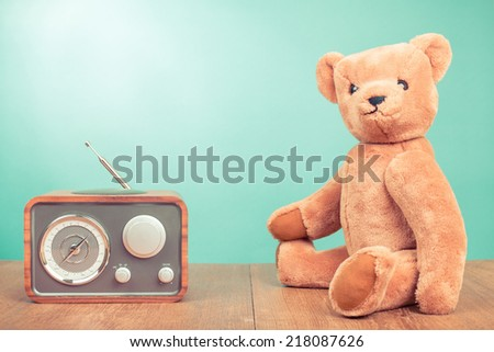 Vintage Teddy Bear and retro radio front mint green wall background - stock photo