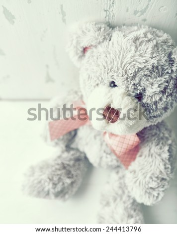 Vintage teddy bear with a pink ribbon - stock photo
