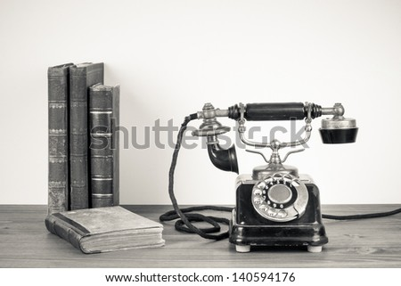 Vintage telephone, old books on table sepia photo - stock photo