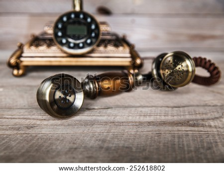 Vintage Telephone on an Old Wood Table - stock photo