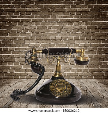 Vintage telephone over the wall - stock photo