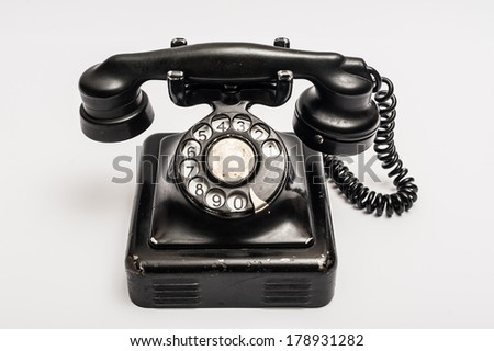 Vintage telephone with rotary dial on a white background - stock photo