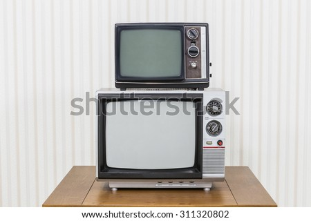 Vintage television stack on old wood table. - stock photo