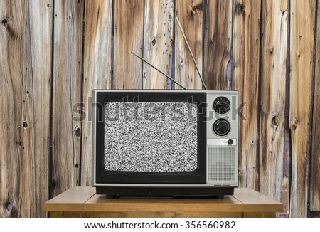 Vintage television with rustic wood wall and static screen.   - stock photo