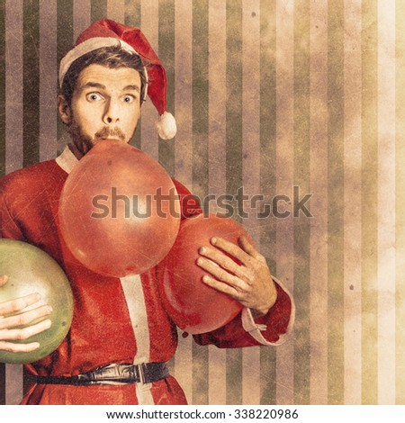 Vintage textured christmas card concept on a santa man blowing up party balloon in preparation for a happy holiday event. Xmas copyspace celebrations - stock photo