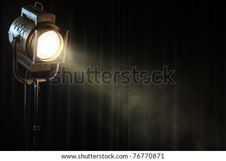 vintage theater spot light on black curtain with smoke