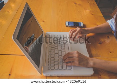 Vintage tone, A woman is working by using wireless network to connect Laptop and mobile phone on the table. Woman's hand typing on laptop keyboard.