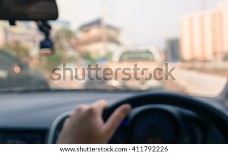 vintage tone blur image of people driving car on day time for background usage. (take photo from inside).