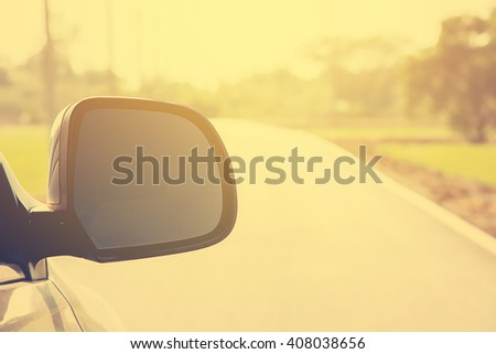 Vintage tone blur image of side view mirror car on the road in countryside with sunlight. Filtered process. - stock photo