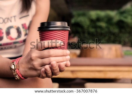 Vintage tone Female hand with paper cup and selective focus.  - stock photo