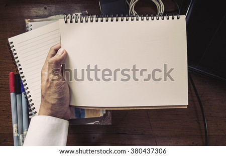 Vintage tone, hand holding notebook on working table - stock photo