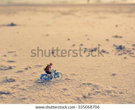 vintage tone image of mini figure dolls biker on the beach blur in background. - stock photo
