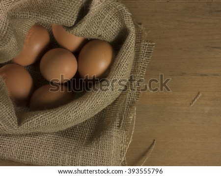 Vintage tone of easter egg with sackcloth on wooden background with copy space,Focus on egg