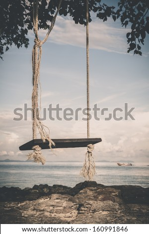 vintage tone picture of swing wooden board by the beach - stock photo