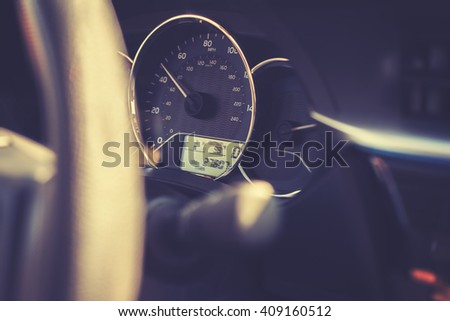 Vintage toned car dashboard with 99 degrees Fahrenheit temperature, shallow depth of field. - stock photo