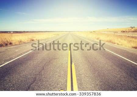 Vintage toned endless country road, travel concept picture.