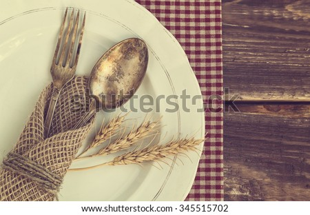 Vintage toned picture of the fork and spoon with the ears of wheat on the old dish at wooden background. Top view. - stock photo