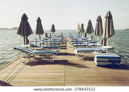 vintage toned pier with beach umbrella and chairs - stock photo