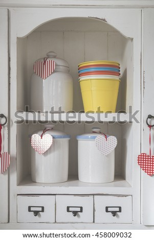 Vintage toned vases in white classic cupboard with drawers and hearts props
