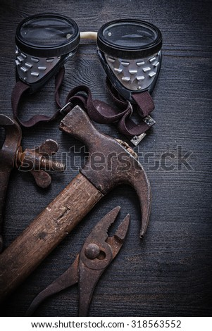 vintage tools  hammer pliers goggles clamp. - stock photo