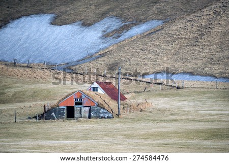 vintage traditional Icelandic farm houses in a valley surrounded by snow covered hills on the southern coast of Iceland during winter. - stock photo