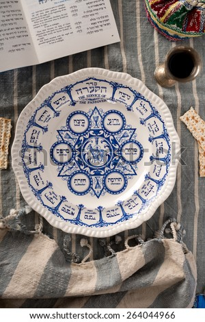 Vintage traditional passover plate, used during the Jewish holiday is show with the habbadah, kiddush cup and colourful yarmulke or kippa in background.  - stock photo