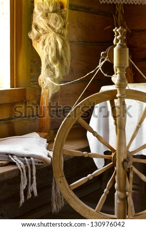 vintage traditional spinning wheel, distaff with yarn in wooden home interior - stock photo