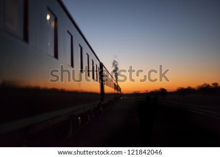 Vintage train going off into the sunset - stock photo