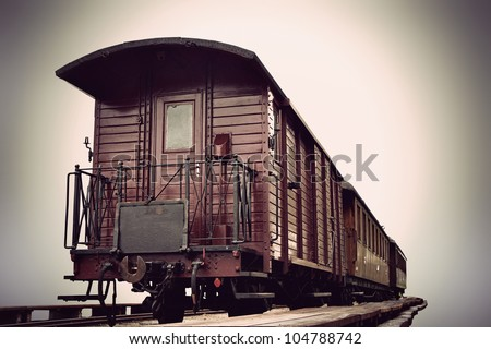 vintage train with wooden cars in sepia tone - stock photo