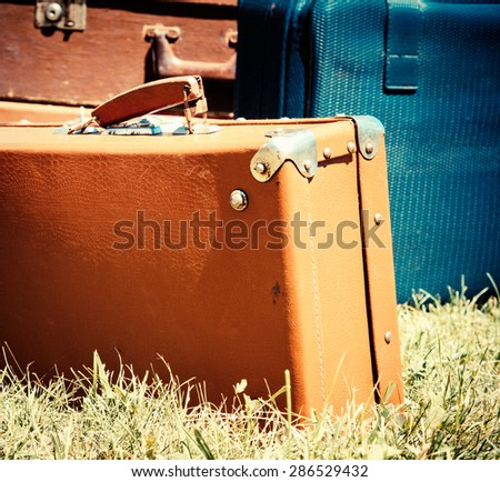 Vintage travel bags and old suitcases. Old leather suitcases at outdoor, film colors toned in retro style. Vintage travel concept with baggage in a warm colors and sun light. - stock photo