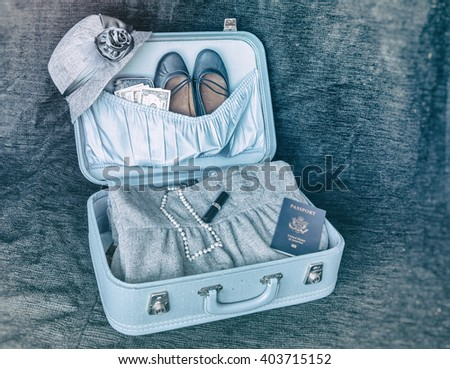 Vintage Travel Suitcase. Open vintage suitcase ready for travel. Containing hat, shoes, dress, pearls, lipstick and passport. - stock photo