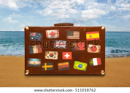 Vintage travel suitcase with stickers on sea background