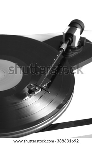 Vintage turntable in silver case playing a vinyl record. Vertical photo isolated on white background closeup