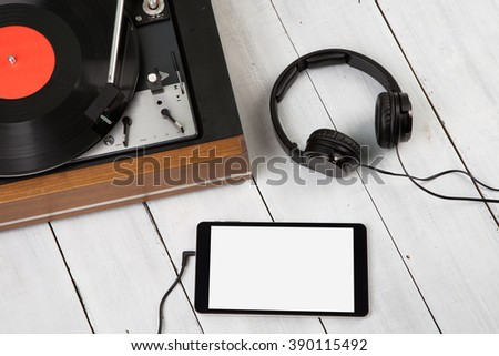 Vintage turntable, phablet and headphones on the wooden background - stock photo