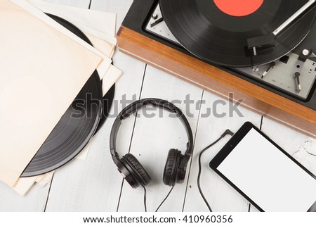Vintage turntable, smartphone and headphones on the wooden background - stock photo