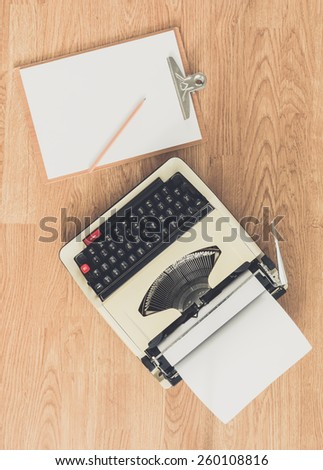 Vintage typewriter and a blank sheet of paper, retro style - stock photo