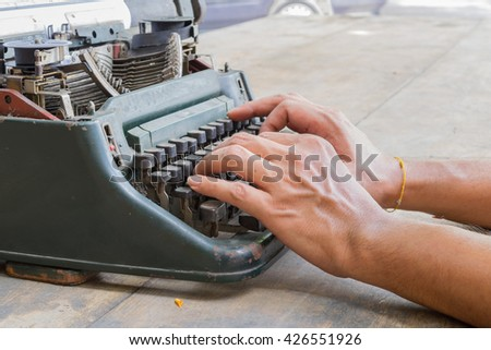 Vintage typewriter and human hand on a wood table - stock photo