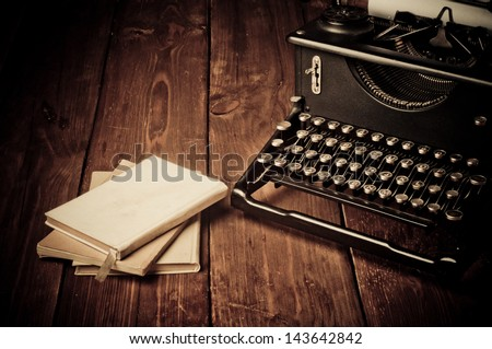 Vintage typewriter and old books, touch-up in retro style - stock photo