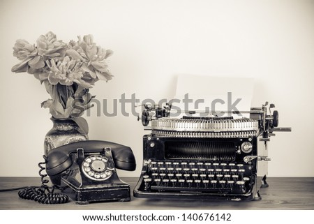 Vintage typewriter, old telephone, flowers on table sepia photo - stock photo