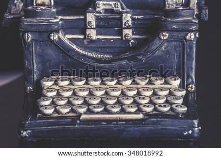 Vintage typewriter with stone carved keys photographed with shallow depth of field. Selective focus image cross processed for vintage look - stock photo