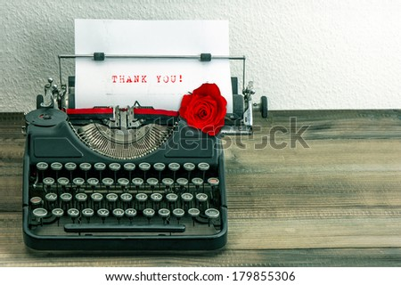 vintage typewriter with white paper page and red rose flower. sample text Thank You! - stock photo
