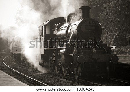 vintage unmarked steam train entering old fashioned station