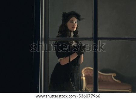 Retro victorian woman in black dress standing behind window holding