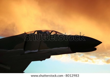 Vintage Vietnam era fighter plane flies off into the sunset - stock photo