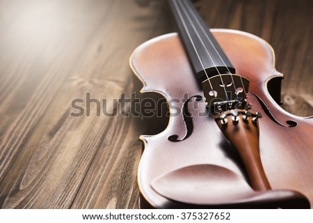 Vintage violin on the brown wooden background. - stock photo