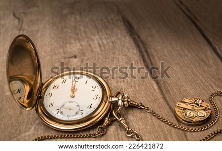 Vintage watch on a wooden background showing five to twelve, text space - stock photo