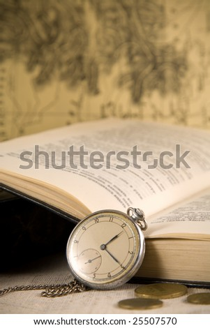 Vintage watches, book, and coins over blurred map background