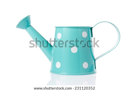 Vintage watering can with turquoise color and polka dots isolated on white background. - stock photo